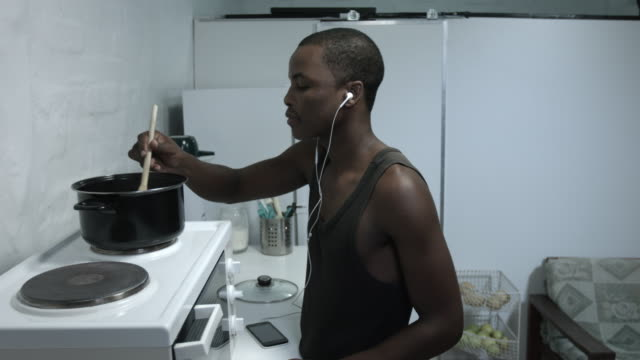 Guy listening and dancing to music while cooking. video
