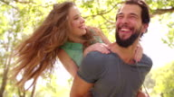 Guy piggybacking his laughing girlfriend in a sunny park video
