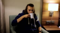 guy sits down, takes a Cup of tea from the bedside and drink it video