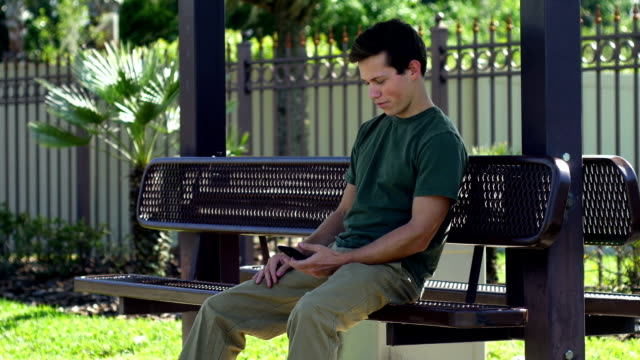 Guy sitting on bench chekcing cell phone video