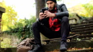 Guy sitting on skateboard and Looking at Smartphone video