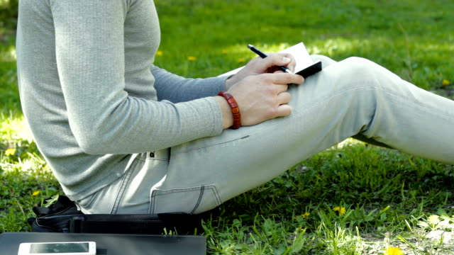 guy sitting on the grass in the Park and makes entries in the notebooks video