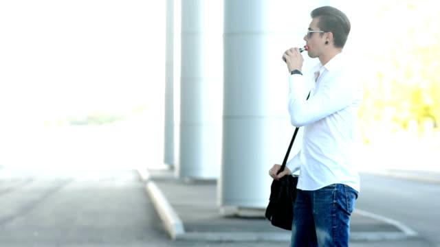A guy smoking electronic cigarette at street closeup exhaling smoke wipe video
