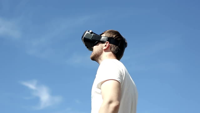 guy uses a virtual reality glasses on the backfound of sky video