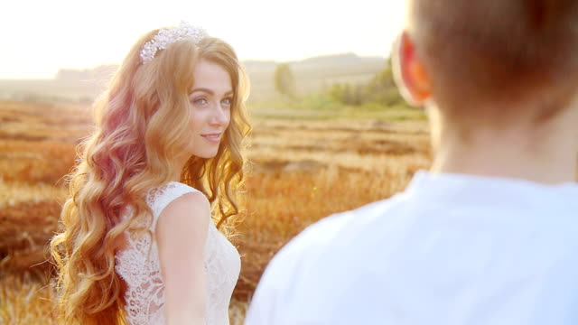 A guy with a girl is walking in a meadow. Romance at sunset. video