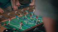 Guys playing tabletop soccer in apartment video