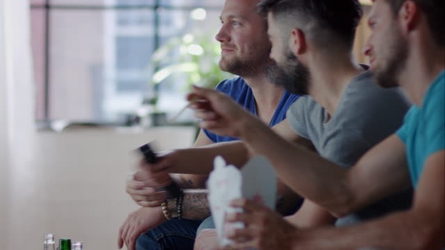 Guys sitting on couch watching funny movie video