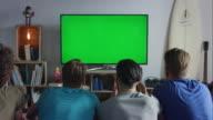Gars assis sur un canapé en regardant la télévision et les acclamations - Vidéo
