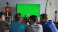 Guys sitting on couch watching tv and clinking bottles video