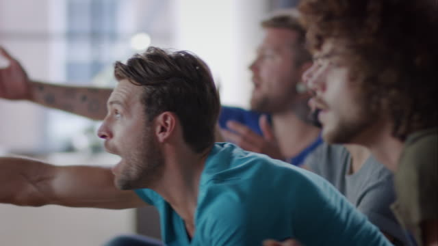 Guys sitting on couch watching tv disappointed video
