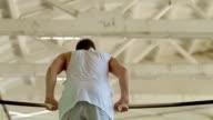 Gymnast spins on horizontal bar. Slow motion video