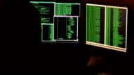 Hacker breaking code. Criminal hacker with black hood penetrating network system from his dark hacker room. video