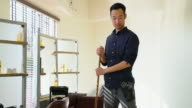Hair dresser sweeping up in his salon video
