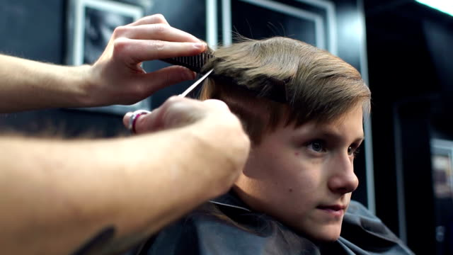 Hairdresser cut child hair in barbershop, slow mo. video