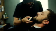 Hairdresser cuts client's beard in Barbershop video