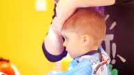 Hairdresser cutting cute childs hair video