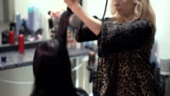 Hairdresser makes hair styling by hairdryer video