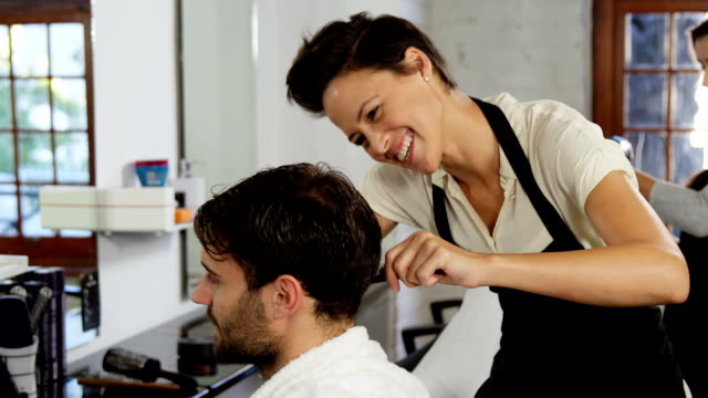 Hairdresser trimming her client hair video