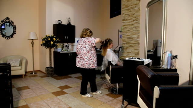 Hairdresser woman dries the hair dryer video