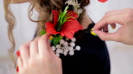 Hairstylist, hairdresser finishing creative hairstyle with flowers for teen girl video