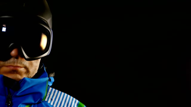 Half face portrait of skier/snowboarder man with glasses on black background video