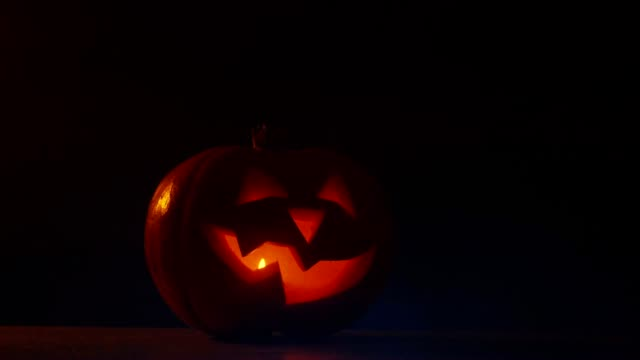 Halloween carved pumpkin Jack-o-Lantern with candles on dark background video