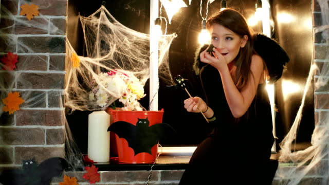 halloween party, teen witch tasting sweets, girl having fun at halloween celebration, trick or treat video