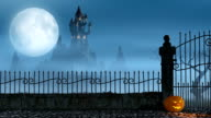 Halloween pumpkins next to a gate of a spooky castle video