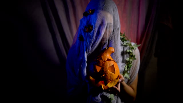 Halloween Witch with a magic Pumpkin in a dark room. Beautiful young woman in witches hat and costume holding carved pumpkin video