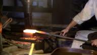Hammer beating glowing metal bar into shape video