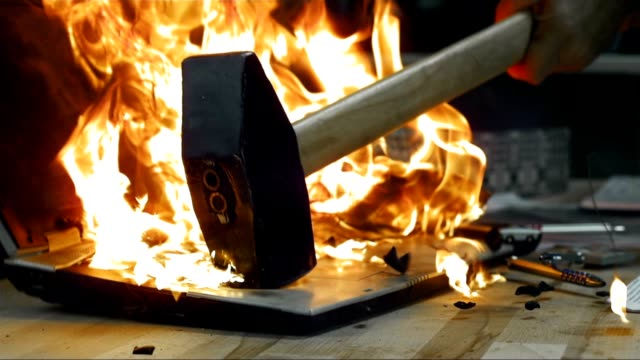 SLO MO LD Hammer hitting a burning laptop video