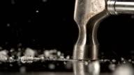 Hammer smashing ice on black background video