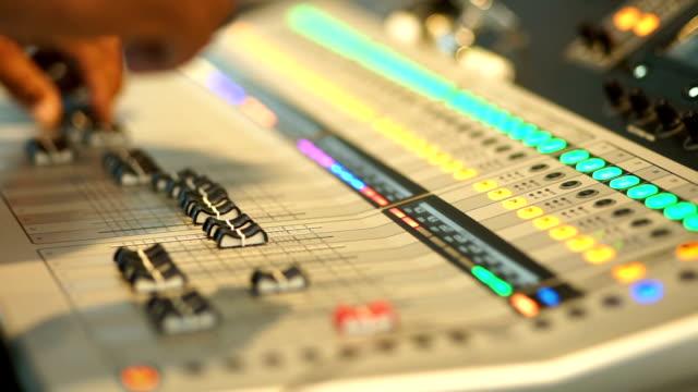 Hand adjusting audio mixer control panel. video