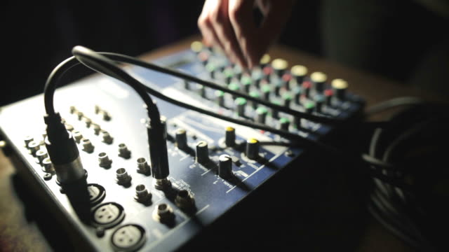 Hand adjusting buttons on sound mixer video