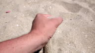 Hand and sand in the desert at sunset. Close up. Slow motion video
