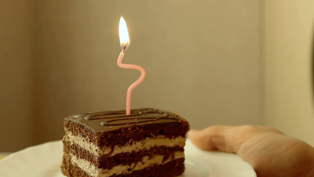 Hand brings a cake with one candle video