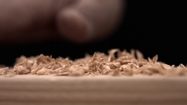 Hand brusing off wood shavings, slow motion video