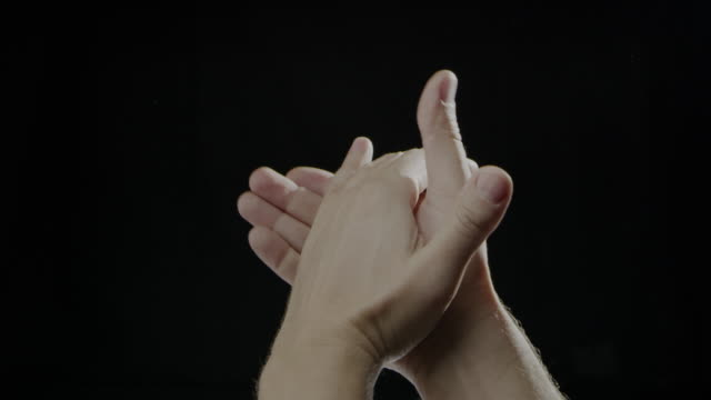 Hand caucasian human clapping slow motion black background video