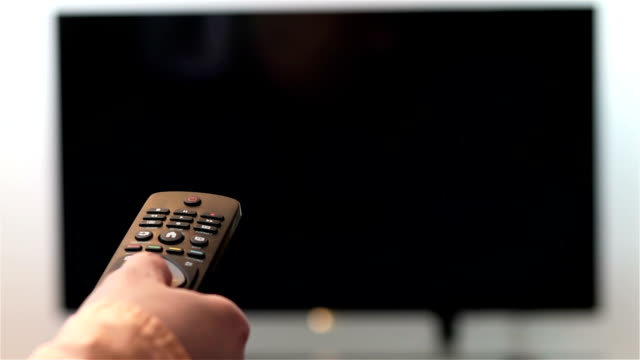 Hand changes the channels on smart TV remote control video