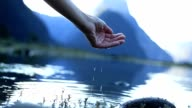 Hand cupped to catch fresh water from the lake-New Zealand video