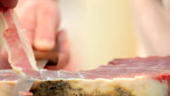 hand cutting a slice of smoked ham video
