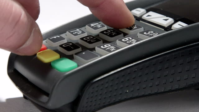 Hand dials the pin code into credit card reader video