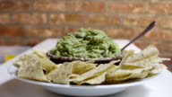 Hand dips tortilla chip in guacamole. video