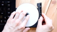 hand ejecting compact disc out of laptop computer video