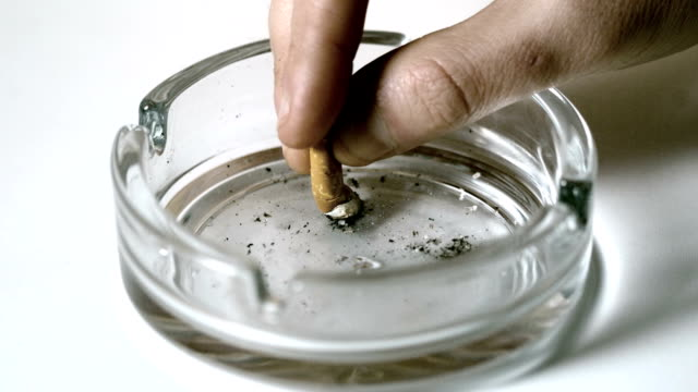 Hand extinguishing cigarette in empty ashtray video