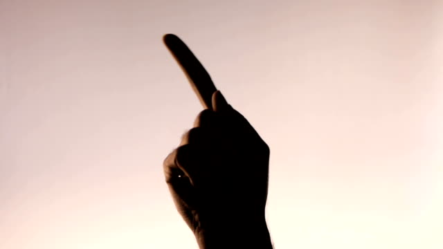Hand gesture. Finger threatening. Silhouetted male hand on gradient pink background video