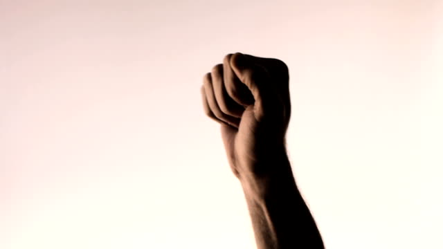 Hand gesture. Fist in the air. Silhouetted male hand on gradient pink background video
