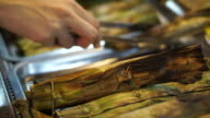 hand grilling Thai food in banana leave. Meat and curry mixed inside video