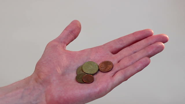 Hand holding a few coins, poverty, little income, family budget video