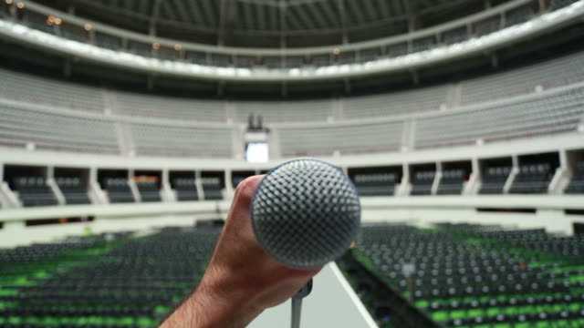 Hand holding a microphone at empty venue. Shot from stage. video